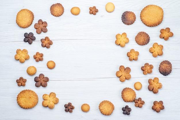 Bovenaanzicht van heerlijke zoete koekjes anders gevormd op licht bureau, koekjeskoekje zoete suiker