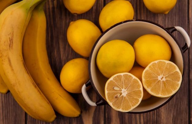 Bovenaanzicht van heldere gele halve citroenen op een kom met citroenen en bananen geïsoleerd op een houten muur