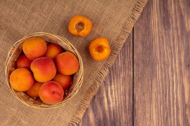 Bovenaanzicht van hele abrikozen in een mand en de helft gesneden op een zak op houten achtergrond met kopie ruimte