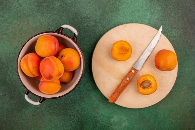 Bovenaanzicht van hele abrikozen in kom en de helft gesneden met mes op snijplank op groene achtergrond