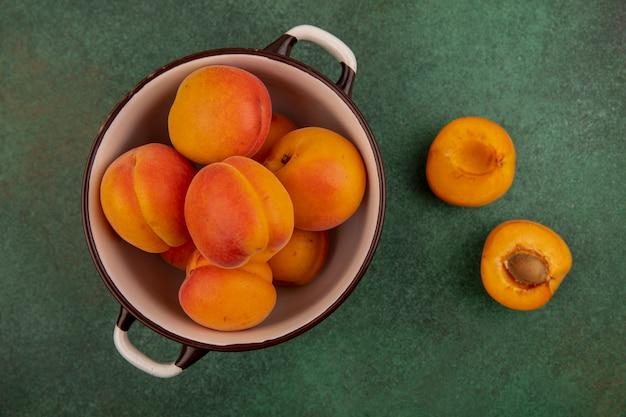 Bovenaanzicht van hele abrikozen in kom en half gesneden op groene achtergrond