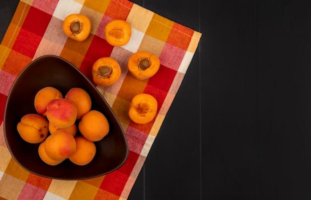 Bovenaanzicht van hele abrikozen in kom en patroon van half gesneden degenen op geruite doek en zwarte achtergrond met kopie ruimte