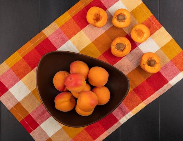Bovenaanzicht van hele abrikozen in kom en patroon van half gesneden degenen op geruite doek en zwarte achtergrond