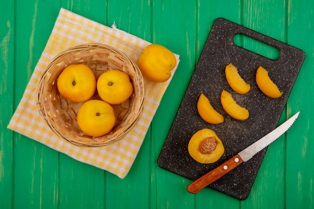 Bovenaanzicht van hele abrikozen in mand en op geruite doek met de helft en gesneden degenen met mes op snijplank op groene achtergrond