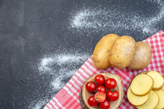 Bovenaanzicht van hele en gehakte rauwe aardappelen op houten plank tomaten aan de linkerkant op zwart wit mix kleuren achtergrond