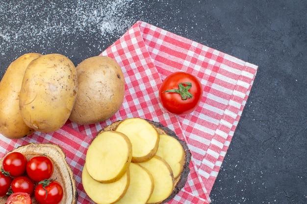 Bovenaanzicht van hele en gehakte rauwe aardappelen op houten plank tomaten aan de rechterkant op zwart wit mix kleuren achtergrond