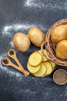 Bovenaanzicht van hele en gehakte verse aardappelen op houten plankkruiden op zwart-witte mixkleurenachtergrond