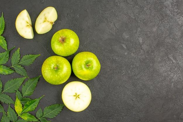 Bovenaanzicht van hele en gehakte verse groene appels en munt op zwarte achtergrond