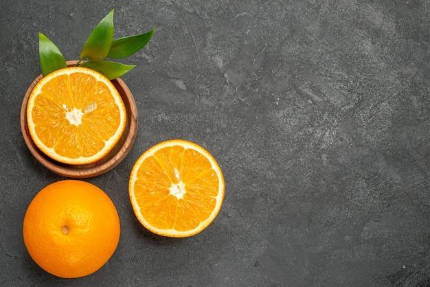 Bovenaanzicht van hele en gesneden verse citroenen met bladeren op donkere achtergrond