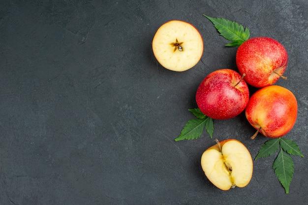 Bovenaanzicht van hele en gesneden verse rode appels en bladeren op zwarte achtergrond