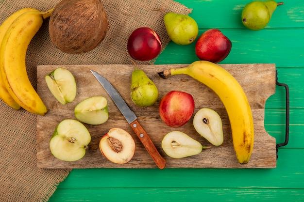 Bovenaanzicht van hele en halve gesneden fruit als peer, appel, perzik, banaan met mes op snijplank en kokos banaan op zak en groene achtergrond