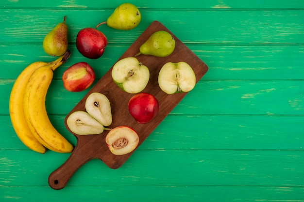 Bovenaanzicht van hele en halve gesneden fruit als peer appel perzik op snijplank met bananen op groene achtergrond met kopie ruimte
