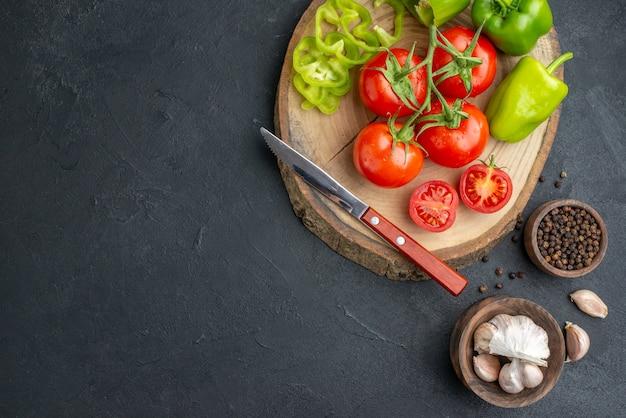 Bovenaanzicht van hele gesneden gehakte groene paprika's en verse tomaten mes op houten snijplank peper knoflook aan de linkerkant op zwart oppervlak