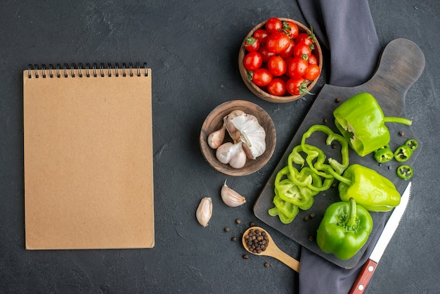 Bovenaanzicht van hele gesneden gehakte groene paprika's op houten snijplank tomaten in kom knoflook tomaten op donkere kleur handdoek op zwart oppervlak