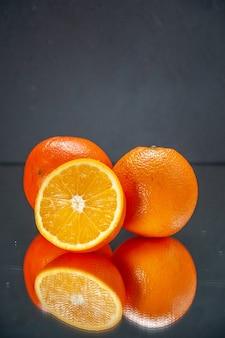Bovenaanzicht van hele gesneden verse sinaasappelen die naast elkaar staan op licht op zwarte achtergrond met vrije ruimte