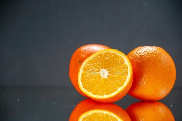 Bovenaanzicht van hele gesneden verse sinaasappelen naast elkaar aan de linkerkant op licht op zwarte achtergrond met vrije ruimte