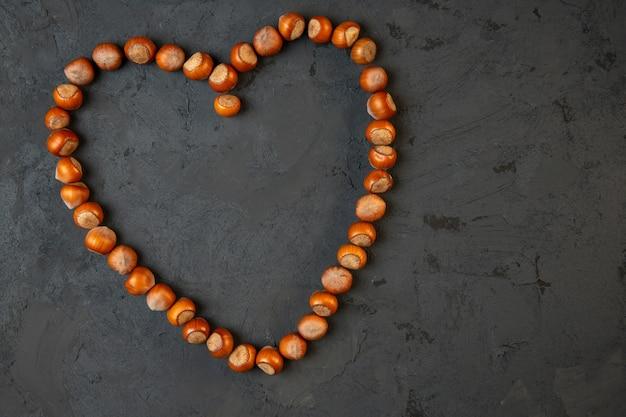 Bovenaanzicht van hele hazelnoten gerangschikt in een hartvorm op donkere j