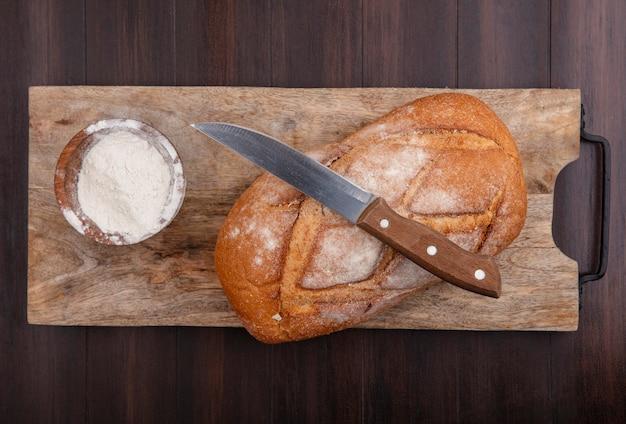 Bovenaanzicht van hele knapperige brood en kom meel met mes op snijplank op houten achtergrond