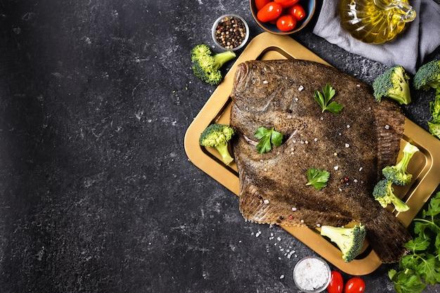 Bovenaanzicht van hele rauwe heilbot vis met groenten op zwarte achtergrond