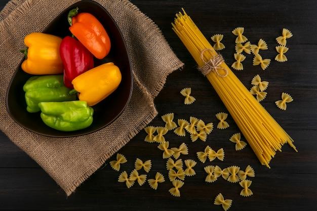 Bovenaanzicht van helften van veelkleurige paprika in een kom met rauwe spaghetti en pasta op een houten oppervlak