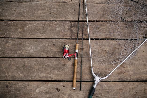 Bovenaanzicht van hengel en net op houten pier