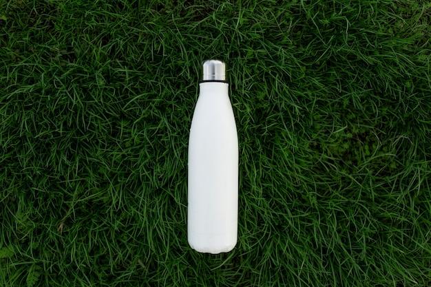 Bovenaanzicht van herbruikbare, eco-stalen thermo-waterfles van witte kleur op groen gras.