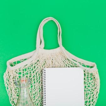 Bovenaanzicht van herbruikbare tas met notebook en glazen fles