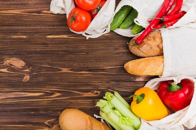 Bovenaanzicht van herbruikbare tassen op houten oppervlak met groenten en fruit