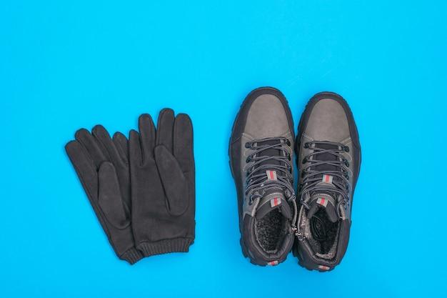Bovenaanzicht van herenhandschoenen en laarzen op blauw. herenschoenen voor koud weer. casual sportschoenen voor heren.