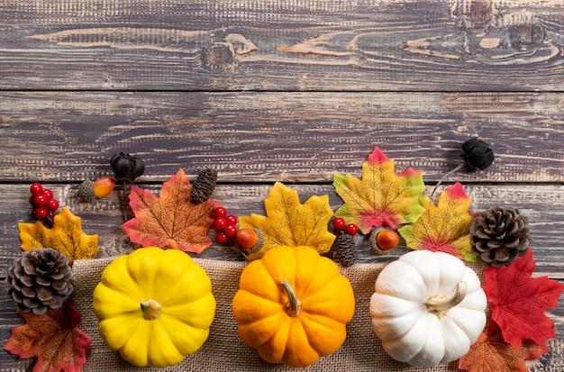 Bovenaanzicht van herfst esdoorn bladeren met pompoen en rode bessen op houten achtergrond. herfst concept of thanksgiving day.