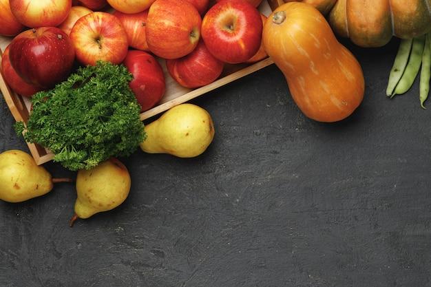 Bovenaanzicht van herfst plantaardige samenstelling met pompoenen en appels op zwarte achtergrond