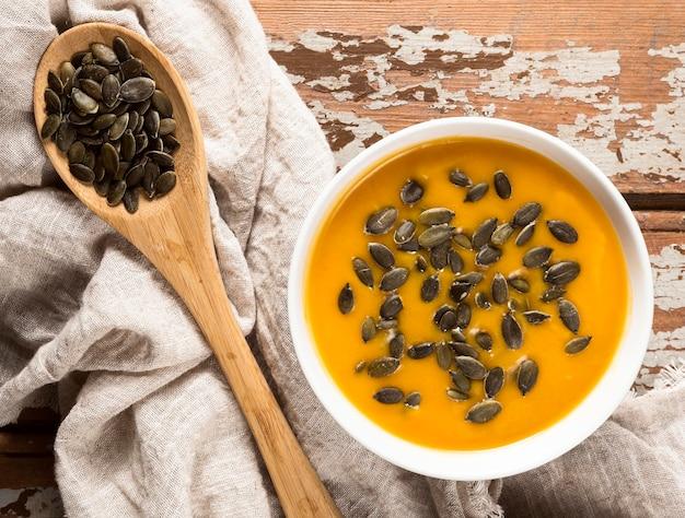 Bovenaanzicht van herfst squash soep met zaden en houten lepel