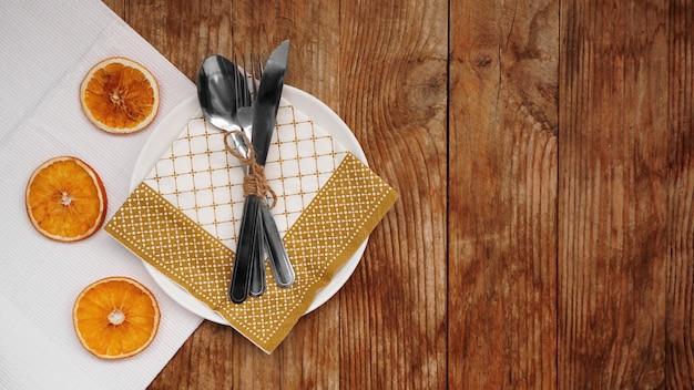 Bovenaanzicht van herfst thanksgiving of kerst tafel instelling over houten tafel met kopieerruimte. witte plaat met droge sinaasappels