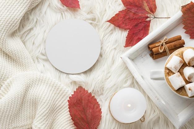 Bovenaanzicht van herfstbladeren en kopje warme chocolademelk op dienblad met marshmallows
