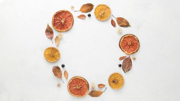 Bovenaanzicht van herfstbladeren met gedroogde citrus