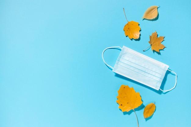 Bovenaanzicht van herfstbladeren met medisch masker en kopie ruimte