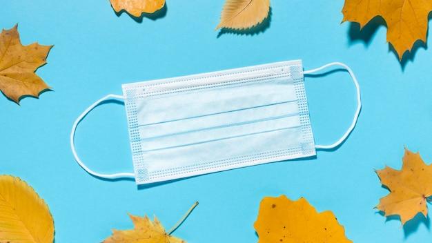 Bovenaanzicht van herfstbladeren met medisch masker