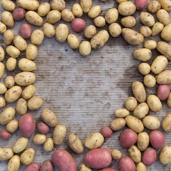 Bovenaanzicht van herfstoogst in hartvorm met biologische aardappelen van verschillende vormen, kleuren en grootte