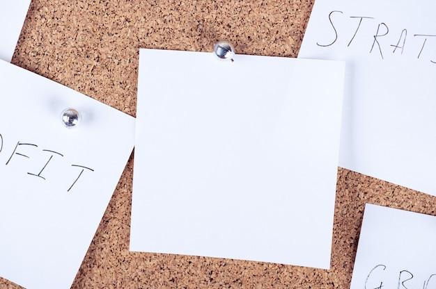 Bovenaanzicht van herinnering plaknotities die aan het kurkbord zijn bevestigd. corticale plank met vel papier. lege plaats voor tekst voor creatief ontwerp. mockup-stijl. aankondigingsconcept