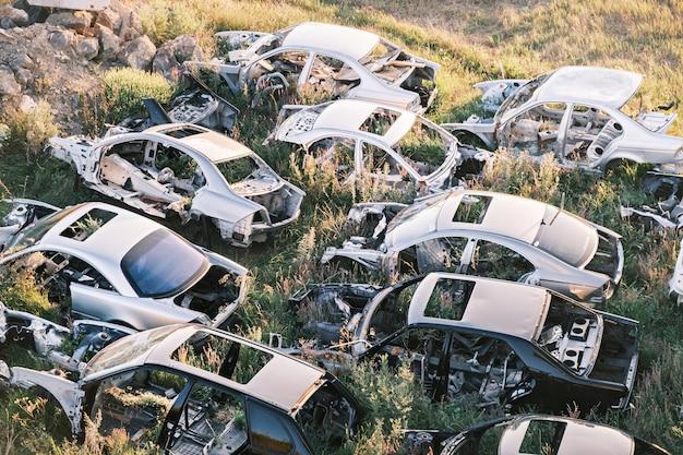 Bovenaanzicht van het autokerkhof gebroken oude roestige auto's die op het gras liggen