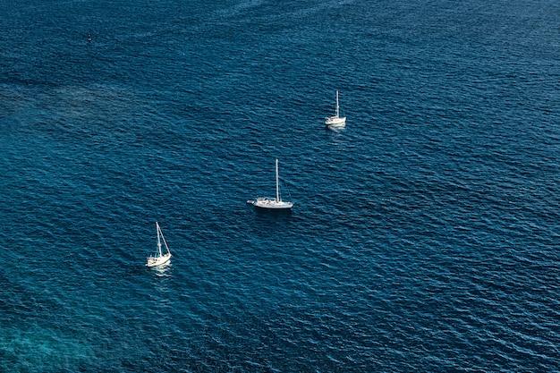 Bovenaanzicht van het blauwe zeewater met prachtig zeiljacht