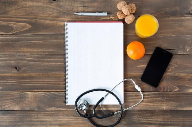 Bovenaanzicht van het bureau van een arts. notebook, stethoscoop en mobiele telefoon op donkere houten tafel.