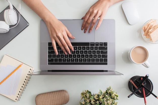 Bovenaanzicht van het bureaublad met laptop en handen