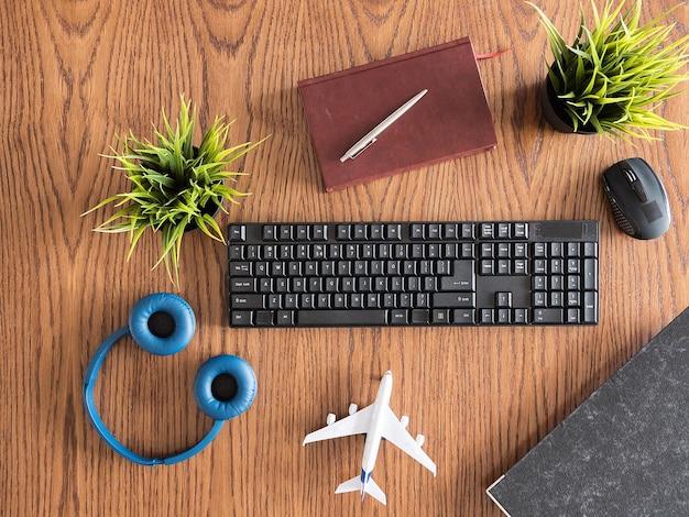 Bovenaanzicht van het bureauconcept van de houten zakenman, pot met gras, koptelefoon, boek, notities