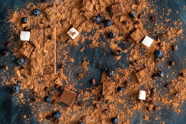 Bovenaanzicht van het cacaopoeder op de donkere tafel plat, chocolade en suiker achtergrond