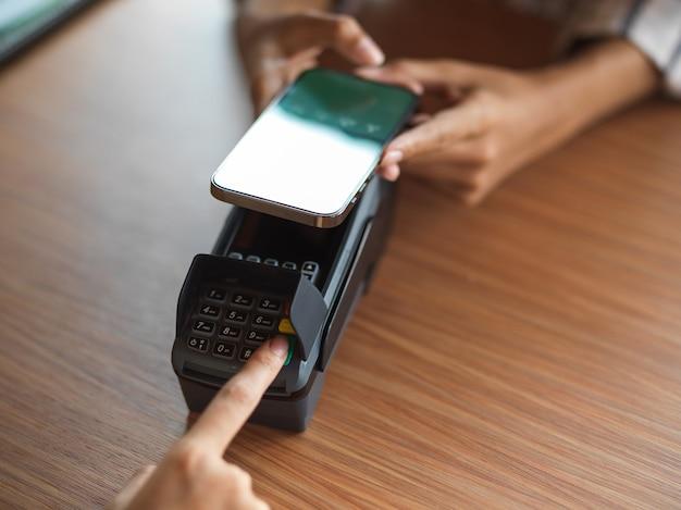 Bovenaanzicht van het gebruik van een betaalterminal via het scannen van qr-codes op het houten bureau via smartphone