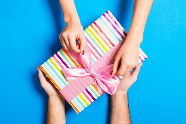 Bovenaanzicht van het geven van een geschenk aan een mooie persoon op kleurrijke achtergrond. paar feliciteren elkaar. feestelijk concept. kopieer ruimte