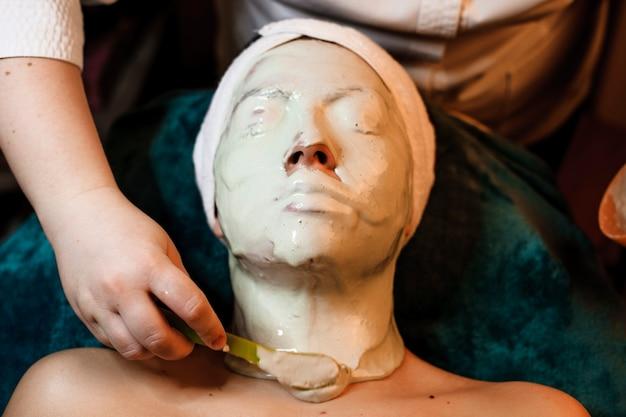 Bovenaanzicht van het gezicht van een vrouw bedekt met een alginaatmasker terwijl ze op een spa-bed leunt. gezicht bedekt met een alginaatmasker terwijl u op een spa-bed leunt.