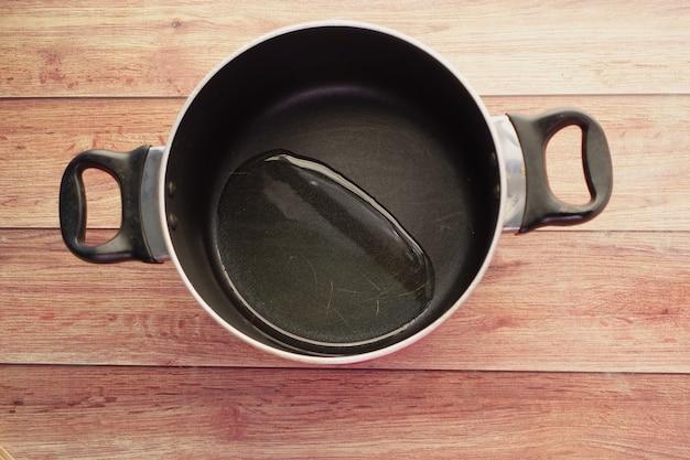 Bovenaanzicht van het gieten van plantaardige olie in de koekenpan