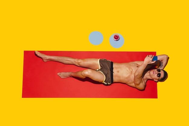 Bovenaanzicht van het jonge blanke mannelijke model dat op het strandresort rust